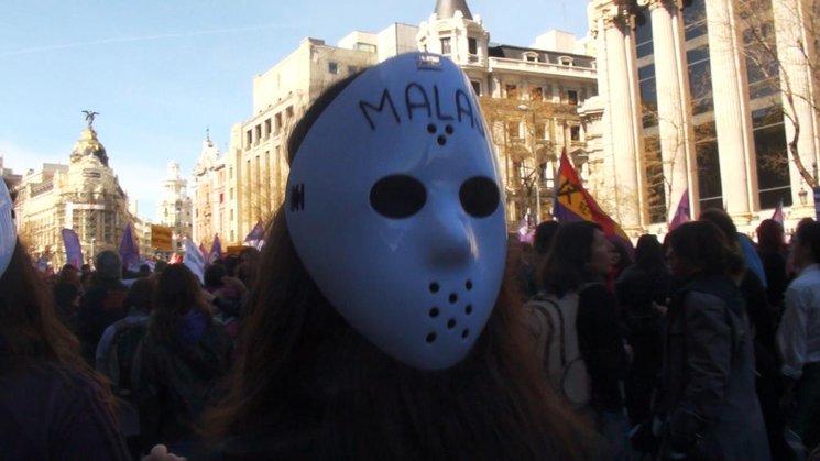 imagen de una mujer con careta en una manifestación