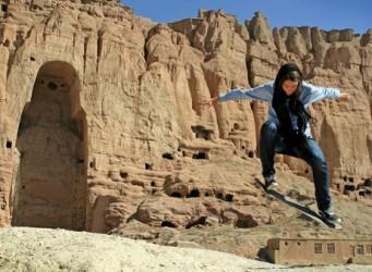 Foto de chica afgana saltando con monopatín