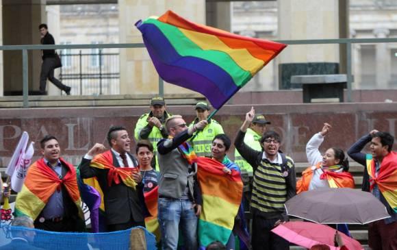 Imagen de manifestantes con una bandera arco iris