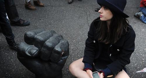 una mujer sentada en el suelo junto a una escultura que representa un puño cerrado