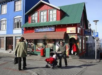 Imagen de un hombre llevando un carrito de bebé en una calle islandesa con