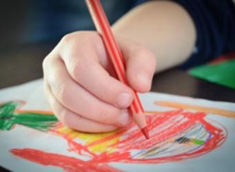Imagen de la mano de un niño o niña dibujando