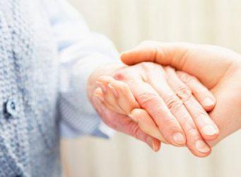 Imagen de las manos de una persona mayor y su cuidadora