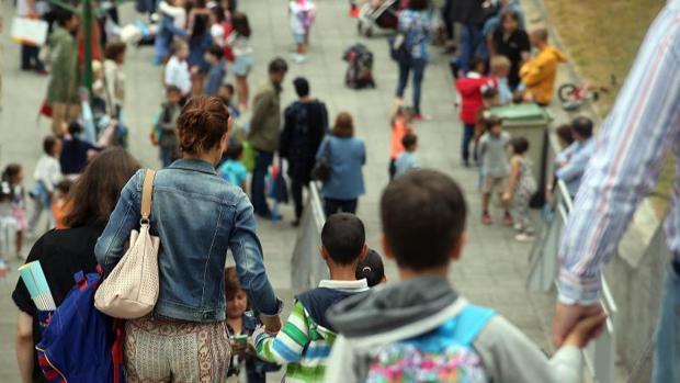 Imagen de un grupo de padres y niños llegando a un colegio