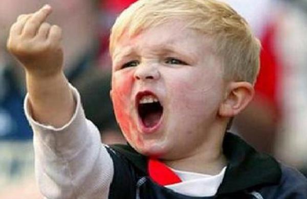 """un niño rubio haciendo el gesto llamado """"peineta"""""""
