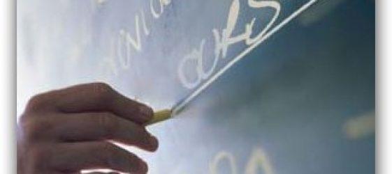 Imagen de una mano escribiendo en una pizarra