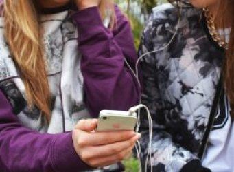 dos jóvenes con teléfonos