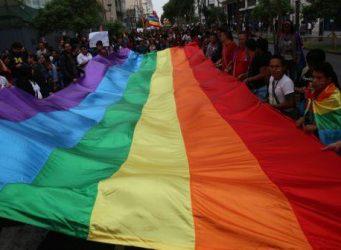 Personas sujetando una bandera LGTBI