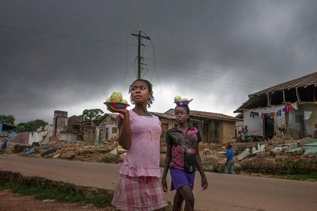 Imagen de dos mujeres comerciando ante unas ruinas en Liberia