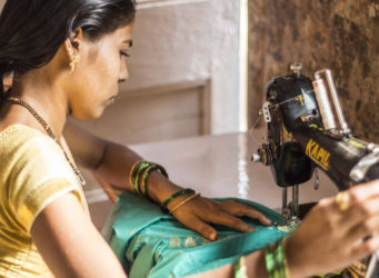 una mujer india cosiendo a máquina