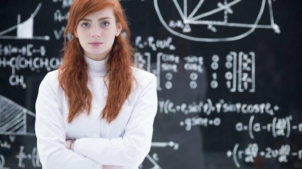 una joven delante de una pizarra llena de fórmulas