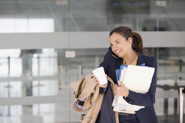 una mujer cargada de papeles sujeta un café y habla por teléfono