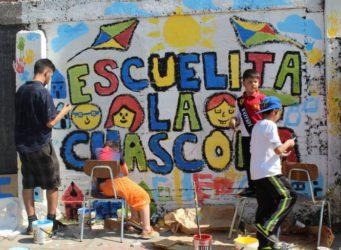 Imagen de niños pintando un cartel