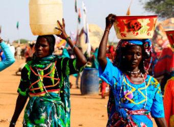 Unas mujeres de Darfur llevan agua