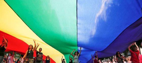 Imagen de participantes en una manifestación con una enorme bandera arco iris