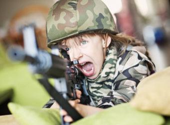 una niña vestida de soldado y con un arma y cara muy agresiva