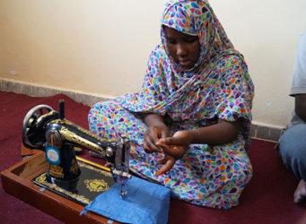 Imagen de una niña en un curso de costura en Mauritania