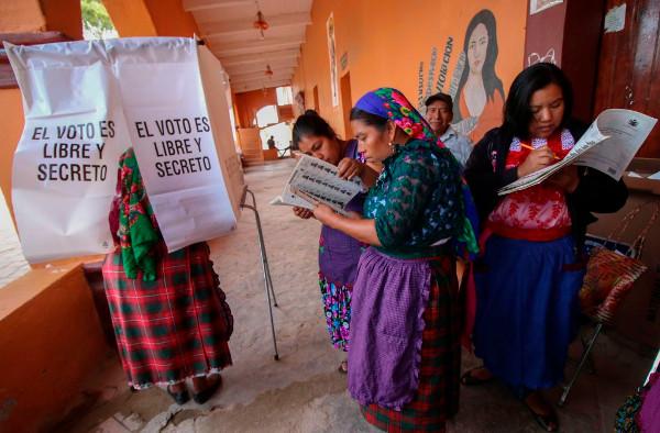 un grupo de mujeres indígenas en una mesa electoral