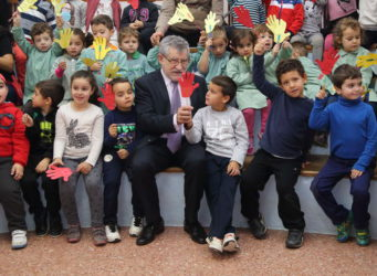 Imagen de un directivo de la Junta con un grupo de niños y niñas
