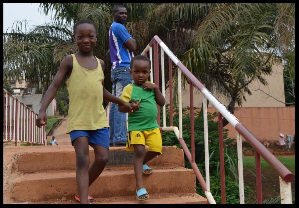 imagen de dos jóvenes cameruneses bajando una escalera con una placa