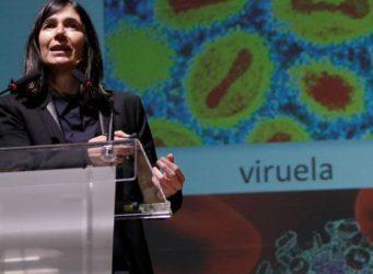imagen de una científica delante de una diapositiva del virus de la viruela