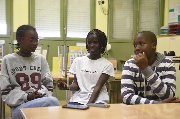 imagen de tres jóvenes hablando ante una mesa