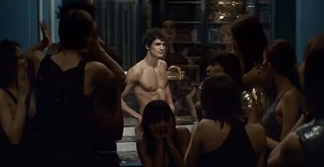 Imagen de un anuncio en el que aparece un hombre semidesnudo rodeado de mujeres
