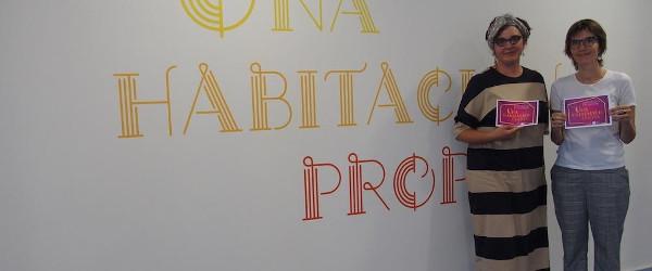 Imagen de dos de las organizadoras delante del cartel de Una habitación propia