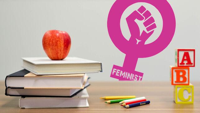 libros sobre una mesa y una manzana con un símbolo feminista