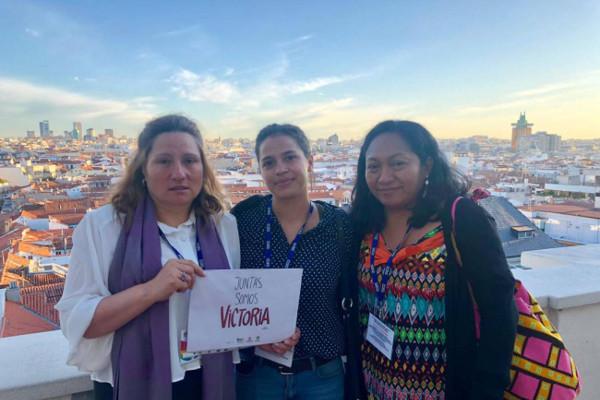 Tres mujeres con el cartel Juntas somos Victoria