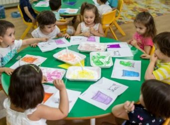 varios nenes y nenas en una mesa pintando
