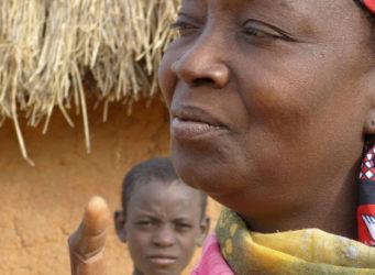una mujer nigeriana delante de una cabaña