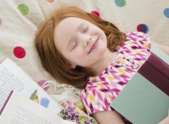 una niña con un libro en las manos y los ojos cerrados sonriente