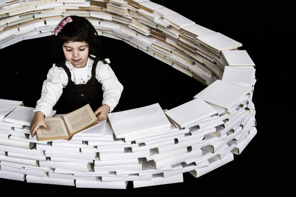 una niña rodeada de libros