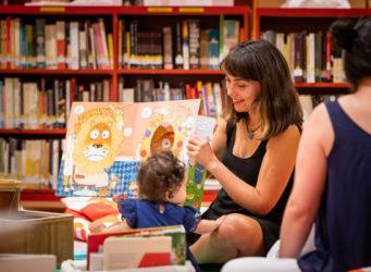 Una mujer lee un cuento a un bebé en un Mall Plaza