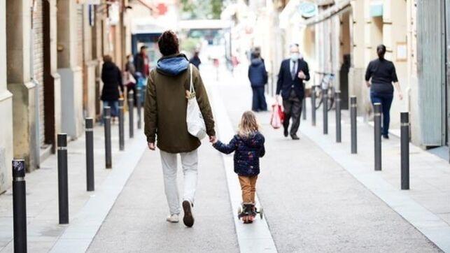 un niño y un adulto pasean por la calle