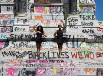 dos bailarinas de color protestan delante de un monumento en Virginia