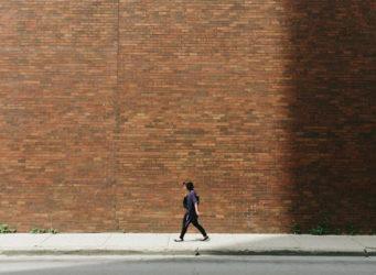 una mujer camina delante de un muro de ladrillo
