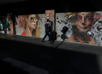 una mujer pasa ante dos murales de mujeres