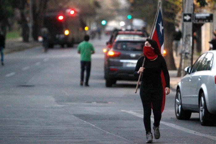 una mujer chilena con la cara parcialmente tapada y una bandera