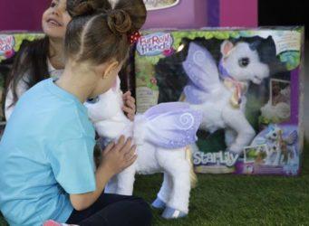 una niña juega con un unicornio