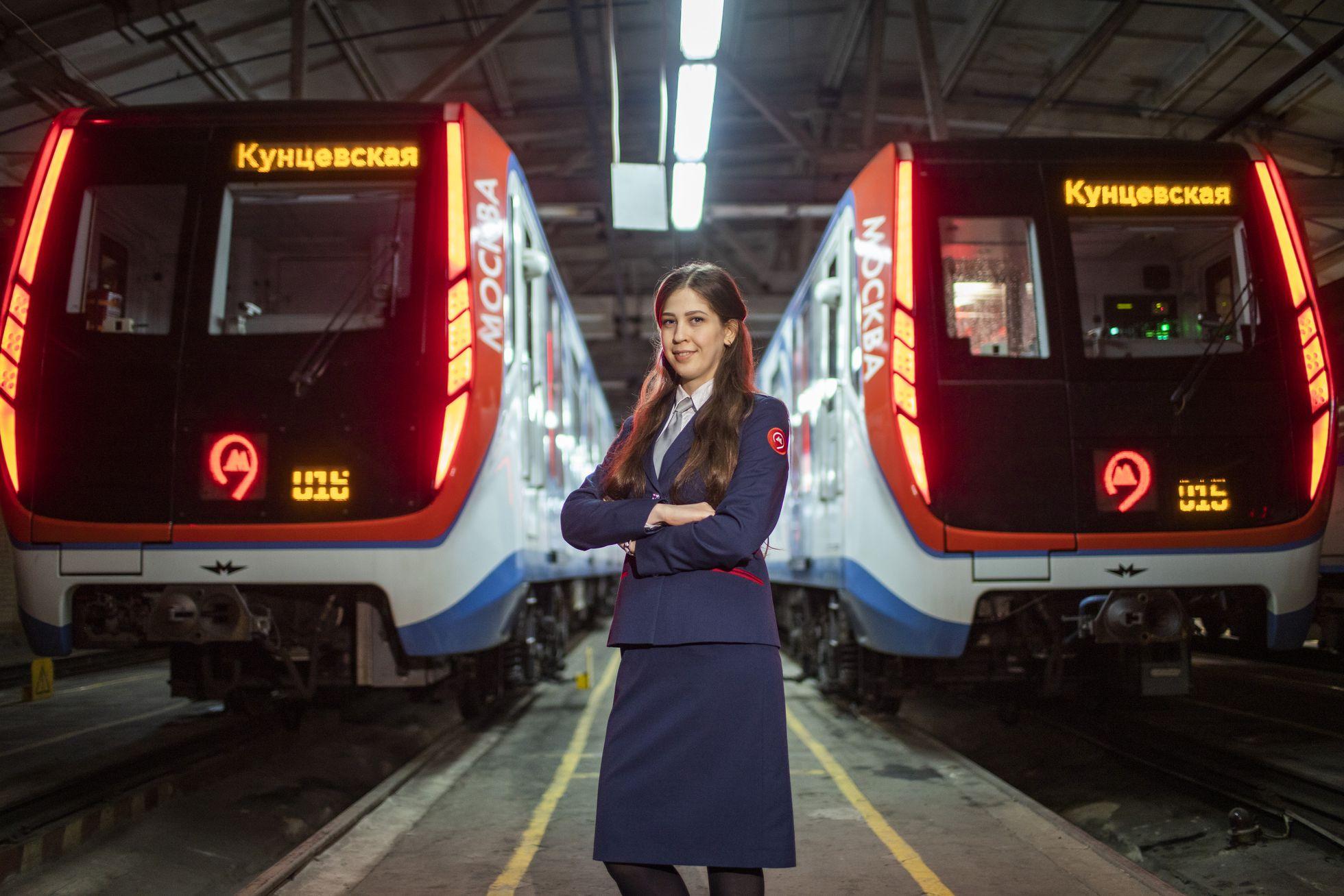 una de las mujeres maquinistas ante dos trenes