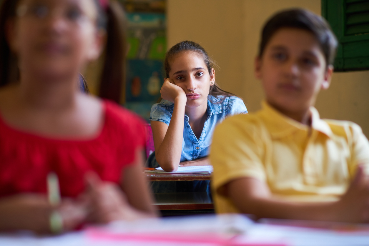 imagen de una niña en una clase con cara de aburrida