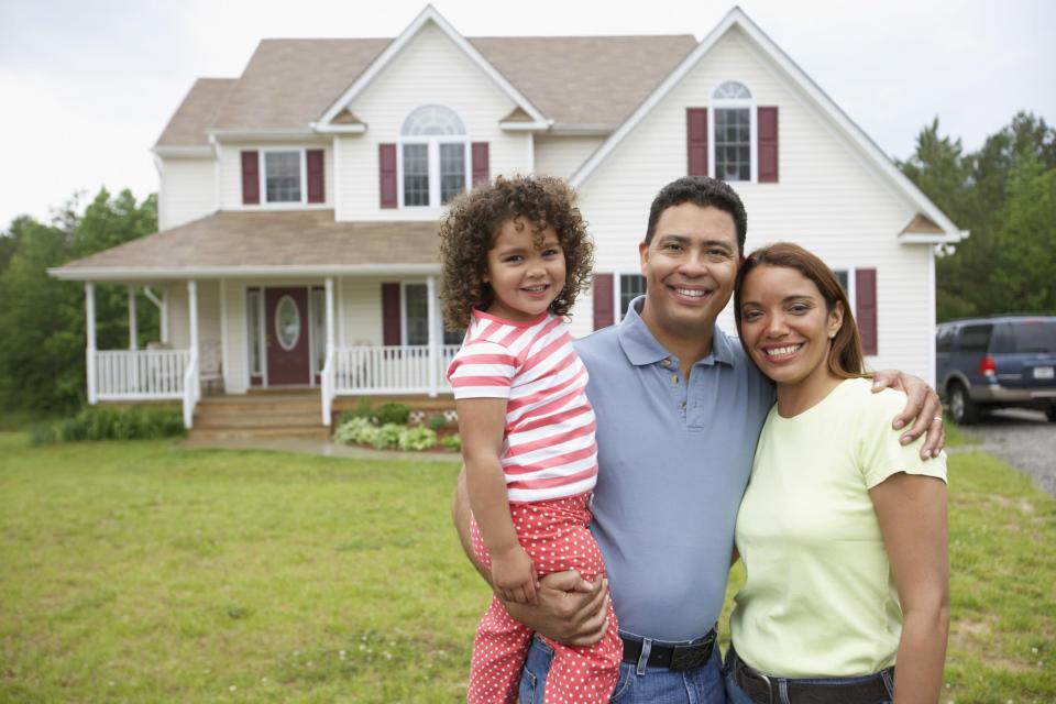 una familia ante una casa y un coche