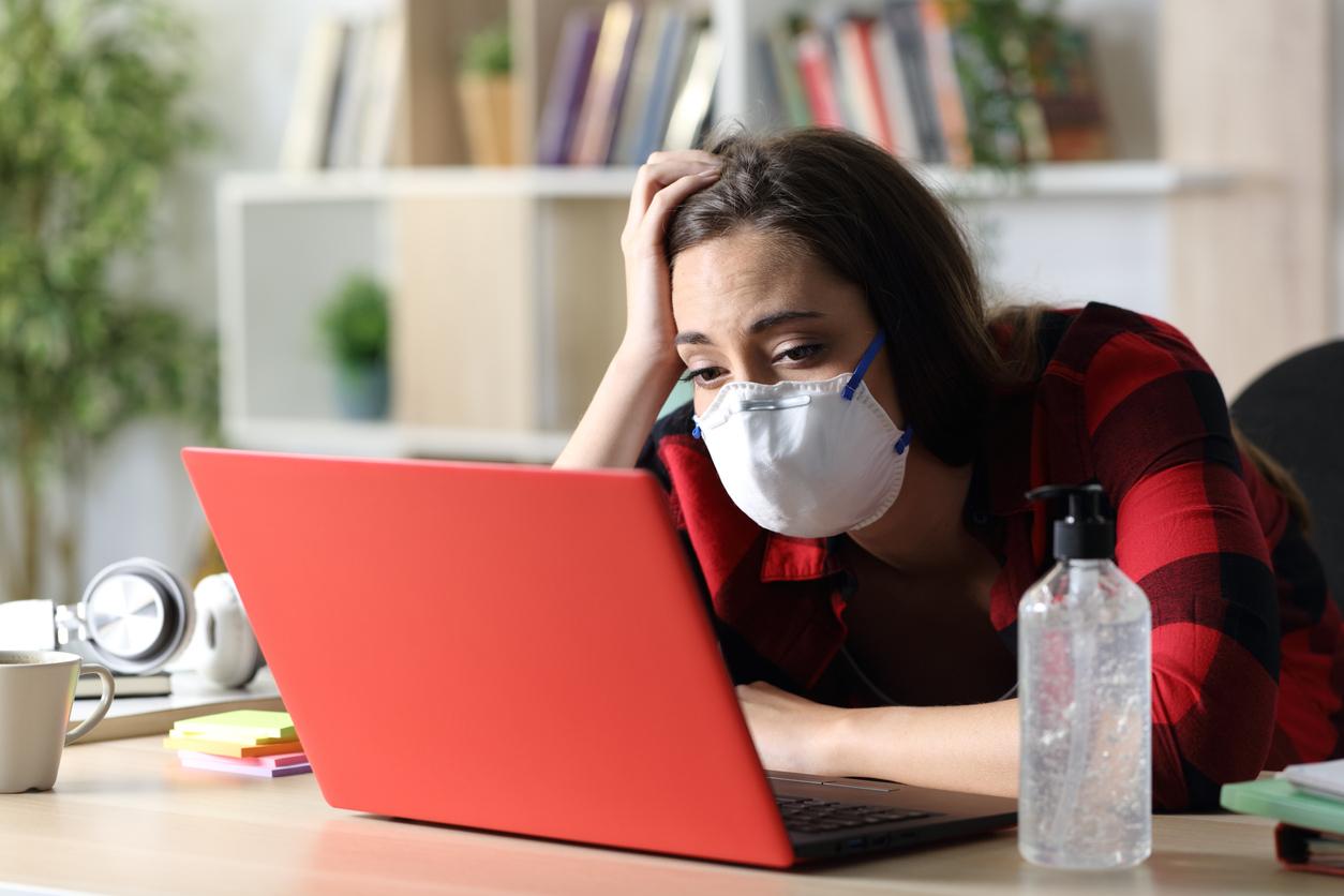 una joven con mascarilla ante un ordenador