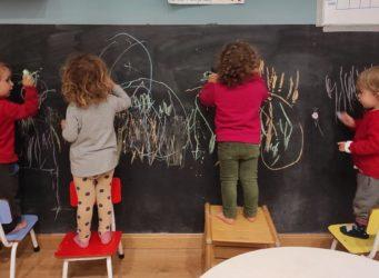 niños y niñas pintan en una pizarra