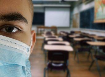 un joven con mascarilla ante una clase vacía
