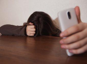 una joven con el teléfono en la mano mira al suelo