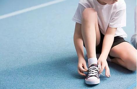 un niño se ata la zapatilla