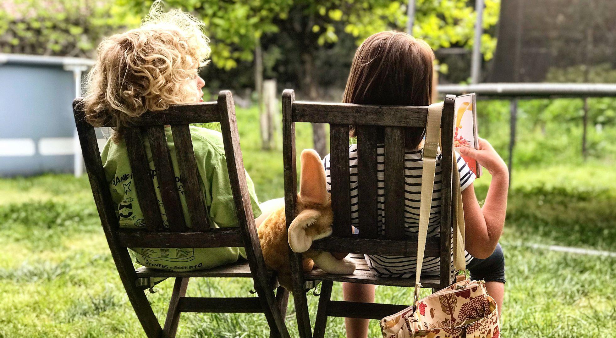 dos niños sentados en sillas en un jardin